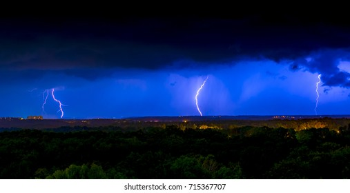 Lightning on the background of the night sky and a stormy cloud over the city.