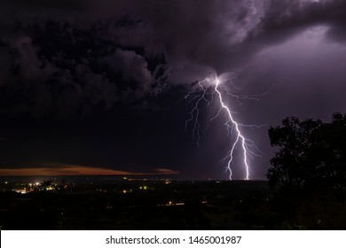Lightning over houses at night during a storm.