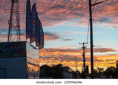 Lightning Ridge, Australia - April 10 2014: Street vendor's slushie van and flags in foreground with colorful sunset in the sky behind.