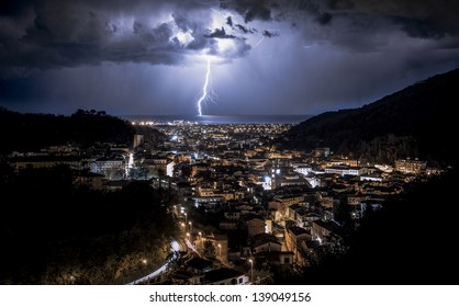Lightning in the sea in front of the city in Italy