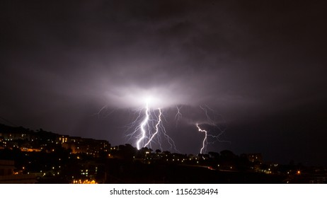 Lightning storm, lightning bolt strike the mountains as a thunderstorm across the sky in the nigh, colours of white and blue electricity and dark buildings in the landscape, Messina, Sicily, Messina