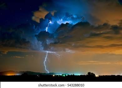 A lightning storm moving over the Phoenix area of Arizona. The blue hues of the lightning is from the white balance setting. The orange glow is from street lights shining up into the storm.