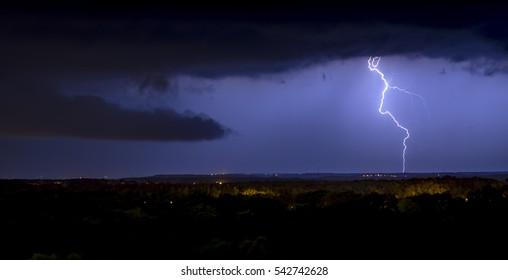 Lightning storm over city in purple light background