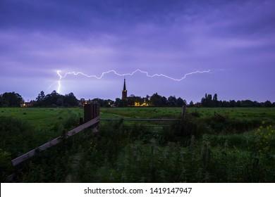 Lightning storm strikes near a small village at in in farmland, Zoeterwoude Zuidbuurt, the Netherlands