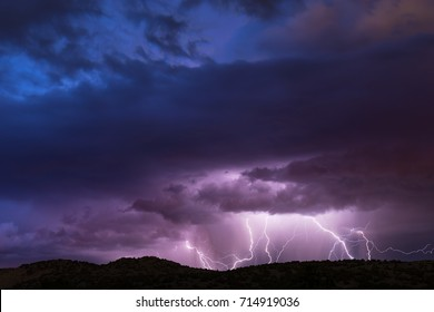 Lightning Strike in the Nevada Desert with colorful sunset clouds.  Sky is moody and dramatic.  Plenty of space for copy.