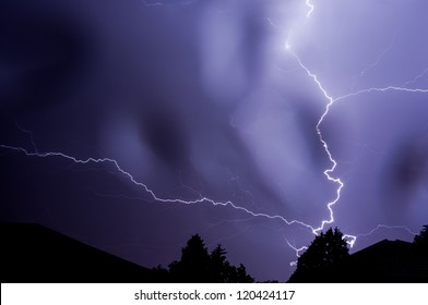 Lightning strike at night behind tree