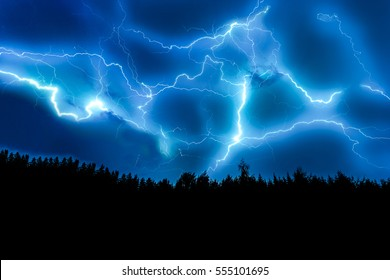 Lightning strike on a dark blue sky over the forest silhouette