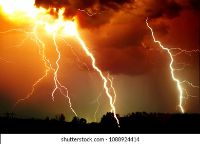Lightning strike on the dark cloudy sky. Orange, yellow and red toned image.