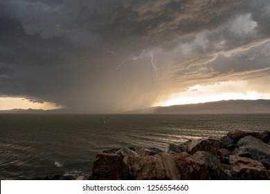 Lightning strike from storm cloud hitting water on lake