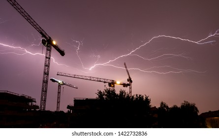 Lightning strikes behind the cranes of a construction site in a thunderstorm