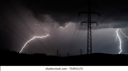 The lightning strikes the high voltage line in a storm.