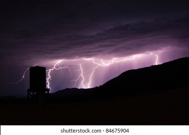 Lightning strikes in the mountains behind an abandoned water tower at Dos Cabezas Siding in the Anza-Borrego Desert.