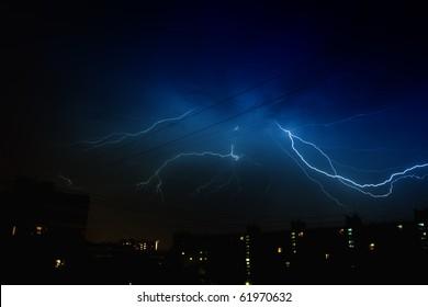 Lightning strikes over dark blue sky in night city