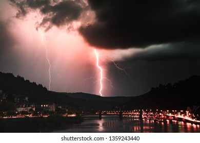 Lightning striking during a summer storm in Heidelberg, Germany. Taken from the old bridge looking east down the Neckar river.