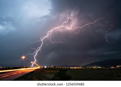Lightning striking the ground near traffic on freeway