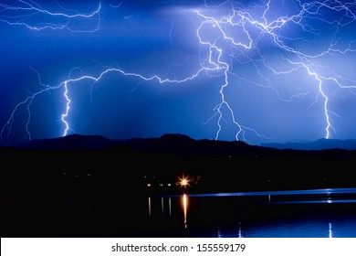 Lightning striking over McIntosh Lake in Longmont Colorado, Boulder County, hitting the foothills of the Front Range of the Rocky Mountains.