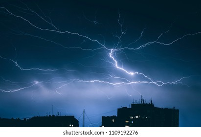Lightning thunderstorm over the city buildings