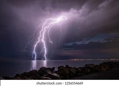 Lightning touching lake at night during rainstorm