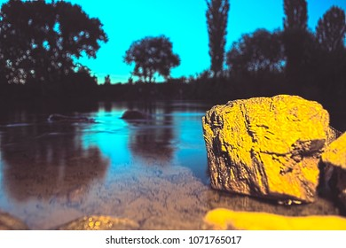 Light-painted rock stone in a shallow shore of river Vardar at golden hour