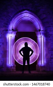 Lightpainting session in a mystical place. Circle shape with a light saber. Silhouette of a man with a light circle behind him. Wooden door of a church  with illuminated gothic sculpture with leds.