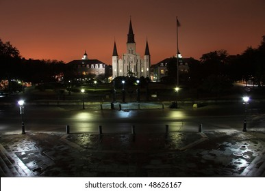 The lights from Bourbon Street reflect off the fog and silhouette St. Louis Cathedral and Jackson Square in the French Quarter of New Orleans, Louisiana