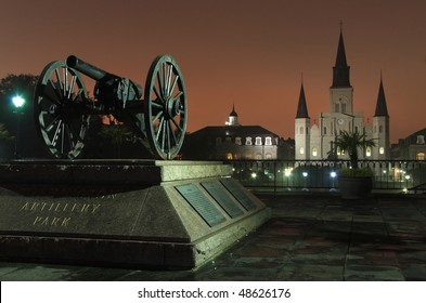 The lights from Bourbon Street reflect off the fog and silhouette St. Louis Cathedral and a vintage cannon in the French Quarter of New Orleans, LA