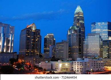 The lights of the Charlotte North Carolina skyline shine in the twilight sky
