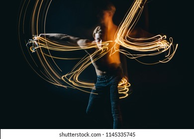 Lights dancer in the dark. Top naked man dynamic movement. Long exposure creative portrait. psychological emotions