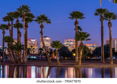 The lights of downtown Phoenix office buildings are reflected in the waters of the Encanto Park lagoon.