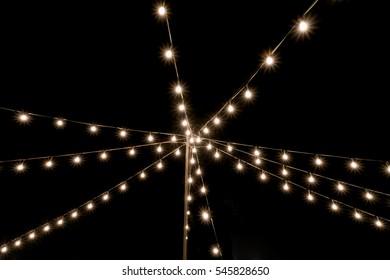 Lights of garland bulbs on dark sky background. Street decoration at winter holidays.