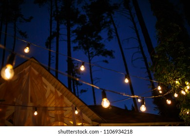 Lights hang overhead on a clear summer night