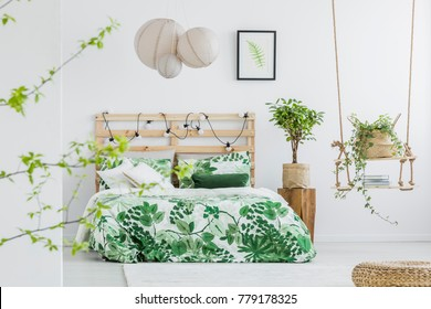 Lights hanging on wooden bedhead in white interior with potted plants and poster