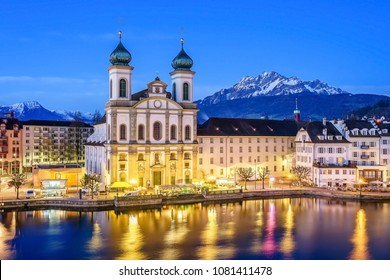 The lights of the Jesuit Church (Jesuitenkirche in German) reflecting in the Reuss river at night in Lucerne, Switzerland