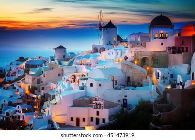 lights of Oia village at night, Santorini Greece, toned