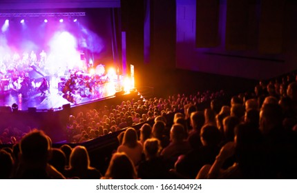 Lights on stage during concert in hall filled with spectators
