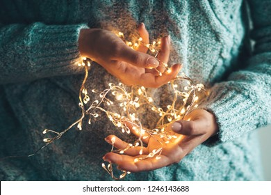lights in the palms. Women's hands holding a garland. Girl in a blue sweater with Christmas lights in her hands, warm Christmas mood, soft focus