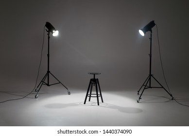 lights in a photo studio on a white background are aimed at a black director's chair