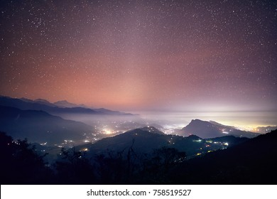 Lights of Pokhara city and villages at night starry sky at mountain range of Annapurna, Nepal