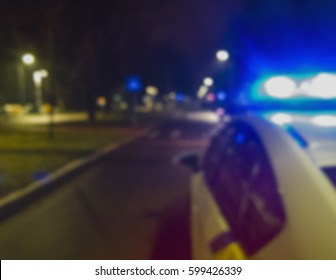 Lights of police car in night time. Night patrolling the city. Abstract blurry image