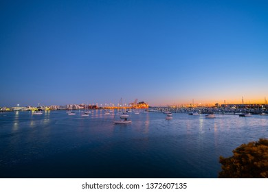 lights of Port of Tauranga ships and harbor at dawn with golden glow of sun on horizon.