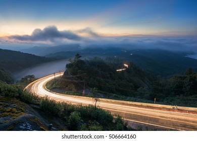 Lights up road to a big mountain in early morning and sunrise sky