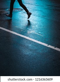 Lights and shadows of New York City. Silhouette of a man running down the street. Reflection of neon lights on wet asphalt