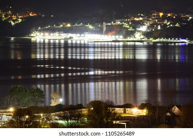 Lights from Shanklin Seafront reflecting from calm seas on the Isle of Wight, UK, with Sandown Bay Holiday Park in the foreground.