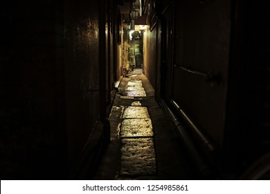 Lights shine at end of dark, narrow alley between city buildings at night