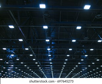 Lights and ventilation system in long line on ceiling of the dark office industrial building, exhibition Hall Ceiling construction