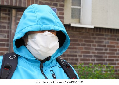 a light-skinned man in a blue jacket, hood, backpack and white face mask against the background of a brick house in the afternoon .during the coronavirus pandemic in Evropa .mask mode
