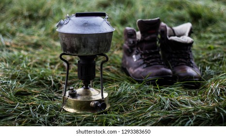 a lightweight aluminium kettle on an old fashioned brass paraffin stove, on wet trampled grass, with a pair of worn brown walking boots beside it