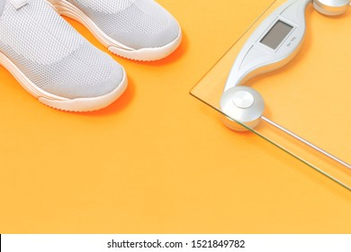 Lightweight modern textile slip on sneakers shoes with weighing scale on saffron yellow background in flat lay with copy space. Weight management and healthy lifestyle sport concept