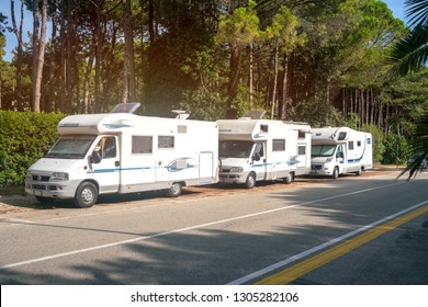 Lignano, Italy, Circa August 2018: three white caravan trailers are parked by a group along the road of the resort town on the embankment street near the beach