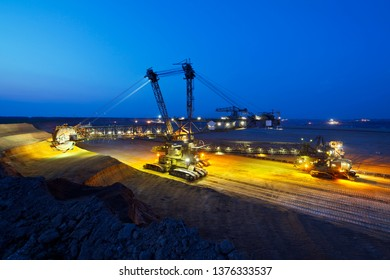 A lignite pit mine with a giant bucket-wheel excavator, one of the worlds largest moving land vehicles with night blue sky.
